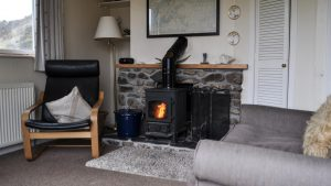 The lounge with woodburning stove at Cruachan Cottage, Cologin